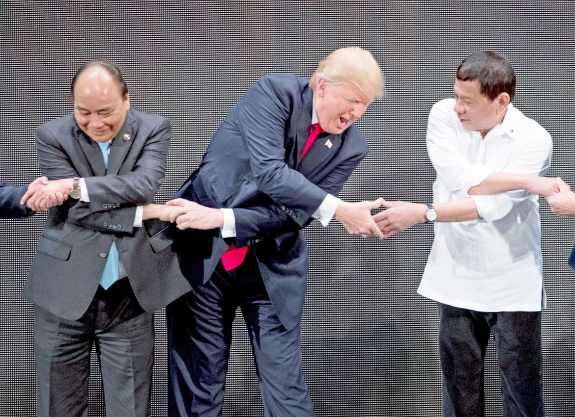 "US President Donald Trump, centre does the ""ASEAN-Way handshake"" with Vietnamese Prime Minister Nguyen Xuan Phuc, left and Philippine President Rodrigo Duterte on stage during the opening ceremony at the ASEAN summit at the Cultural Centre of the Philippines, in Manila Andrew Harnik"